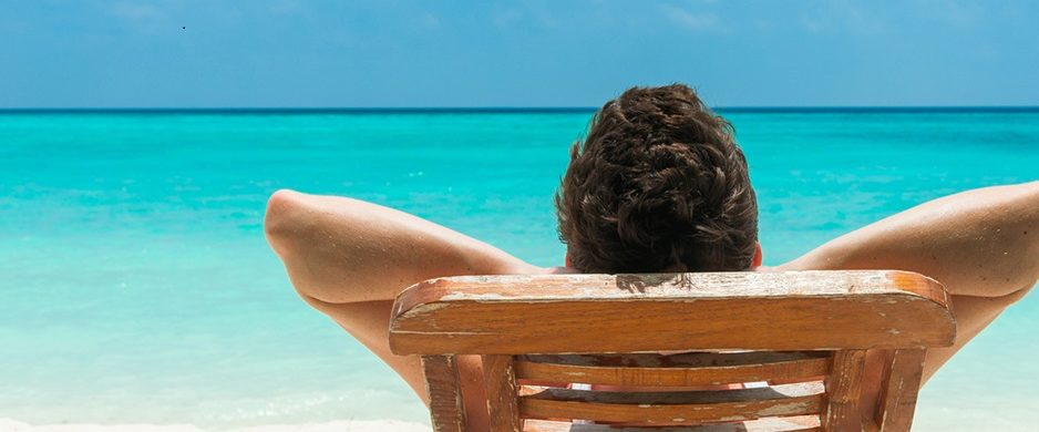 man relaxing in a chair on the beach