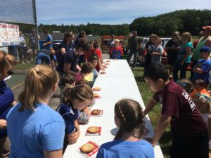 about 12 children ready to start pie eating contest