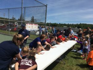 about 12 children enjoying pie eating contest