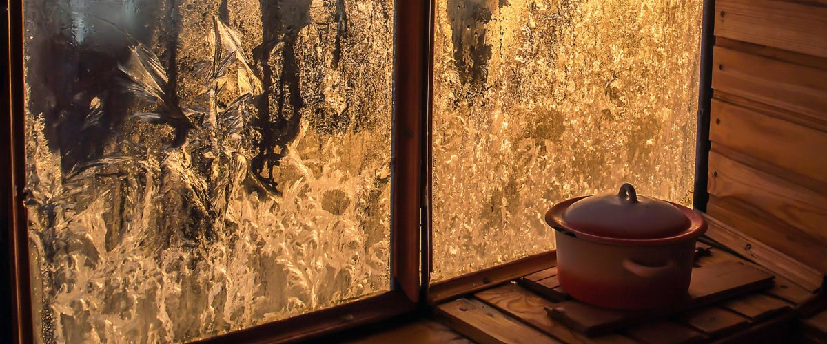 wintery frosted window with kettle on window sill